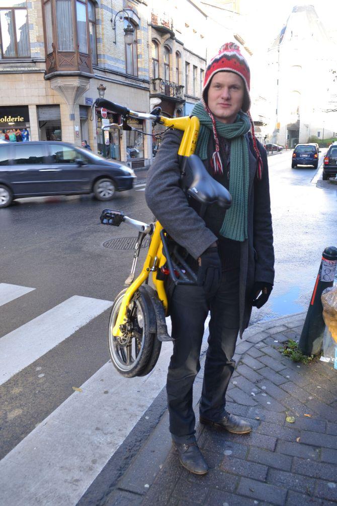 ©Barry Sandland/TIMB: Folded bike on his shoulder