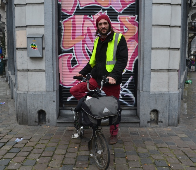 ©Barry Sandland/TIMB - Man with Brompton standing in front of graffiti. covered shutters.