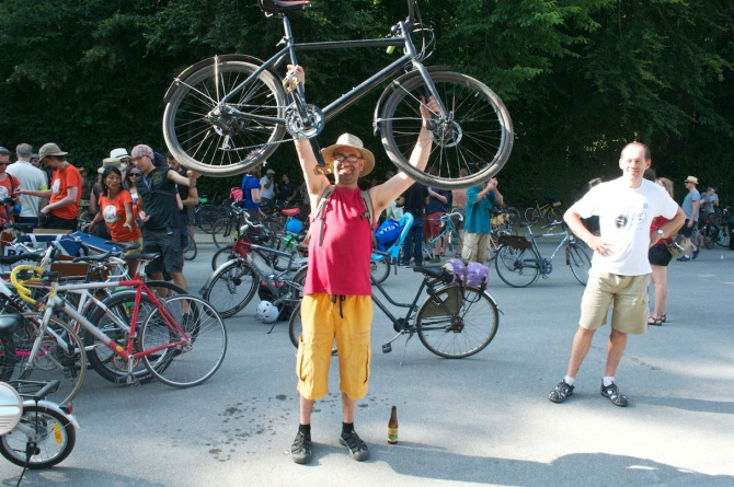 ©Barry Sandland/TIMB - Man hilding his bike aloft at the Bike Parade