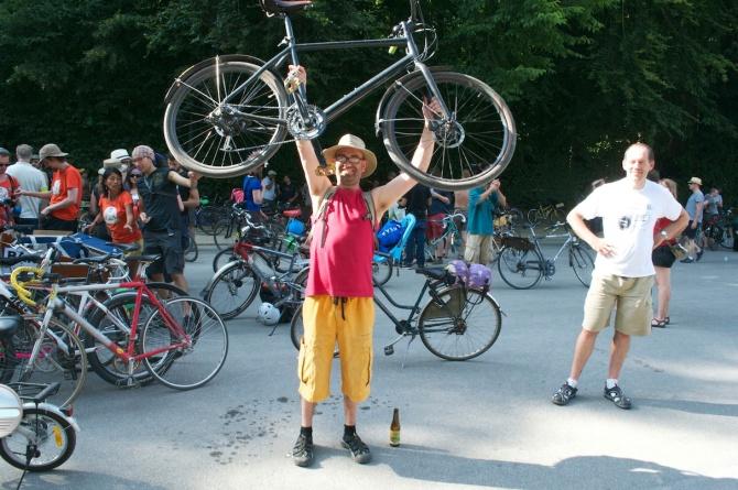 ©Barry Sandland/TIMB - Man hilding his bike aloft at the Bike Parade