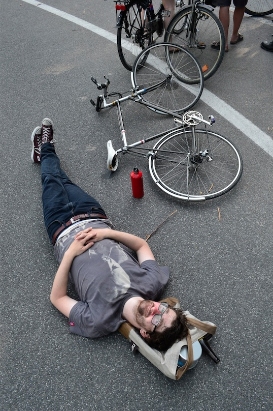 ©Barry Sandland/TIMB - Man resting on the road with his bicycle