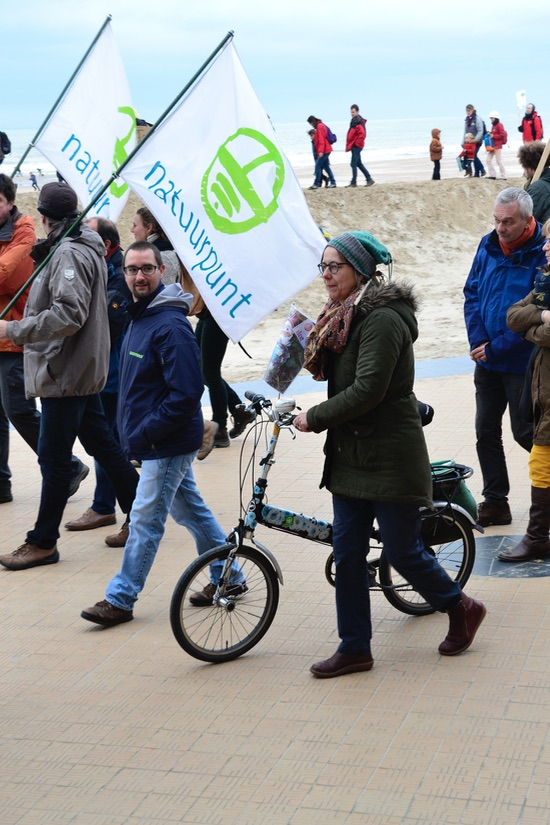 ©B~rry Sandland/TIMB - Woman w folding bike walking at climate change protest in Ostend Belgium