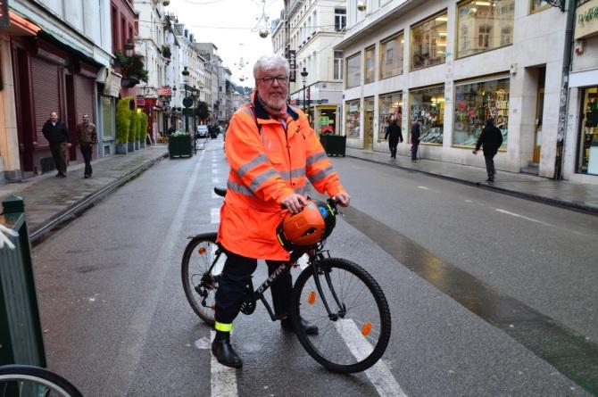 ©Barry Sandland/TIMB - Man in orange jacket w his b-twin bicycle