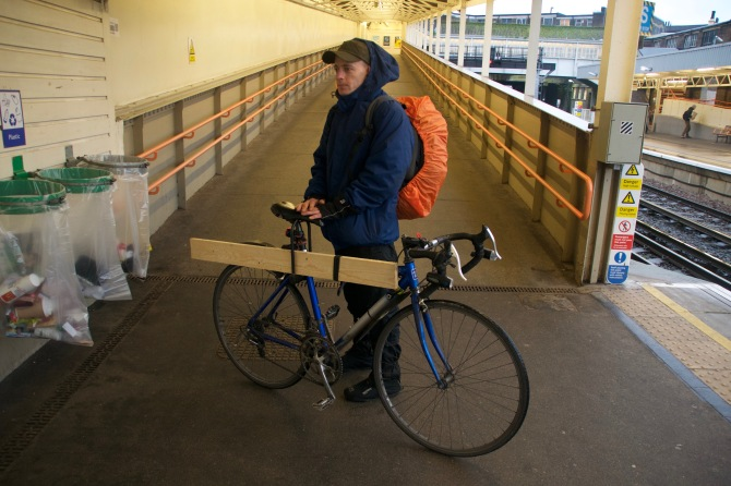 ©Barry Sandland/TIMB - Man and his bike transporting a piece of wood. Photo at National Railway station in the UK