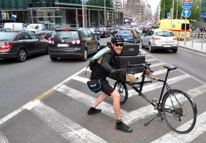 ©Barry Sandland/TIMB - Bicycle courier w a fully laden cargo bike in front of a three hour traffic jam in Brussels.