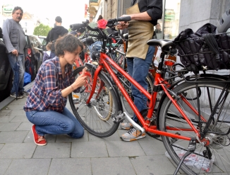 ©Barry Sandland/TIMB - Cycloperativa mechanics helping rider install brake pads to her bicycle