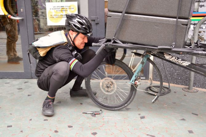 ©Barry Sandland/TIMB - Bicycle messenger repairing flat tire