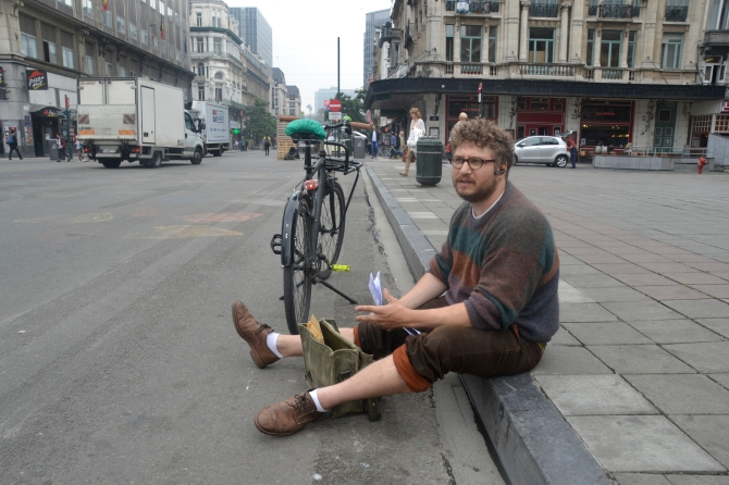 ©Barry Sandland/TIMB - Photographer sitting on the sidewalk near his bike, in Brussels