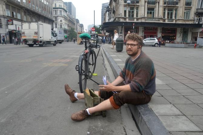 ©Barry Sandland/TIMB - Photographer sitting on the sidewalk near his bike, in Brussels