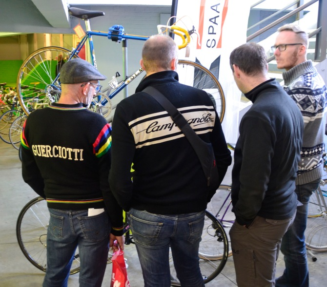 ©Barry Sandland/TIMB - Men staring at an Oleos bicycle at the Stalen Ros vintage market.