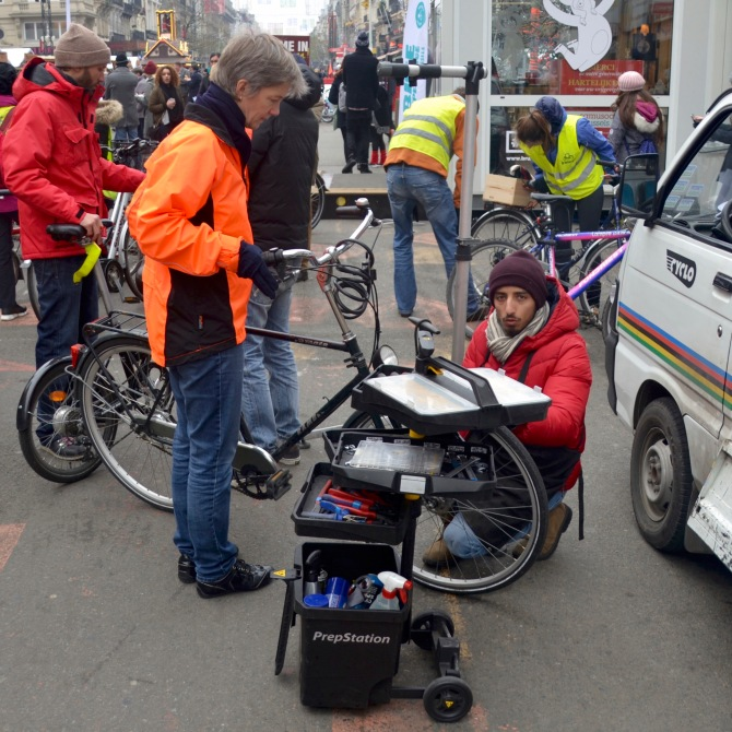 ©Barry Sandland/TIMB - Cyclo mechanics fixing bikes for passerby clients at the Christmas market.