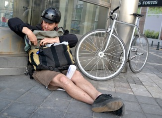 ©Barry Sandland/TIMB - Bicycle messenger sitting on the pavement next to his bike, preparing his carrier bag