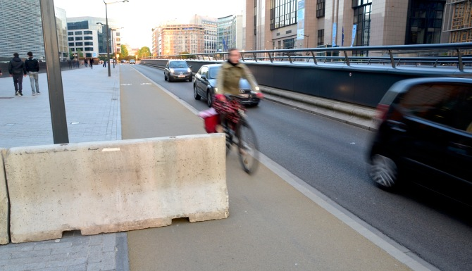 ©Barry Sandland/TIMB - Cyclists passes concrete barriers placed across the bicycle path at the European Parliament