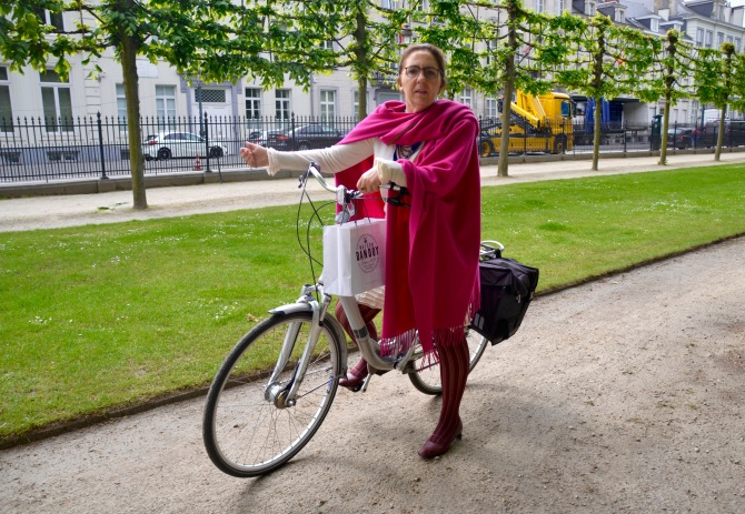 ©Barry Sandland/TIMB - Woman in office dress and red scarf riding through the park on her way to work