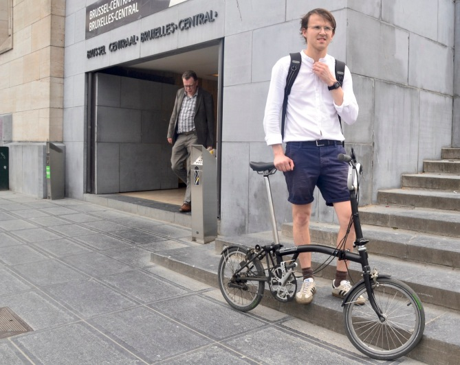©Barry Sandland/TIMB - Rider with his folding bike outside entrance to the train station
