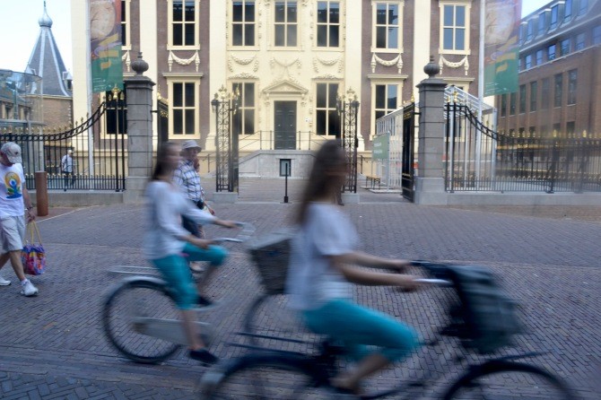 ©Barry Sandland/TIMB - Two cyclists passing in front of a museum in The Hague