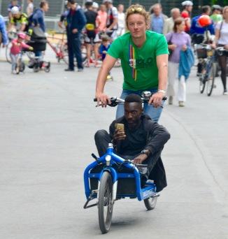 ©Barry Sandland/TIMB - Cargo bike w passenger texting as they ride.