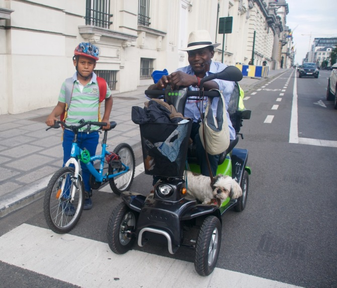 ©Barry Sandland/TIMB - Man in electric wheelchair accompanying his son on a new bike route in the city.