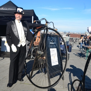 ©Barry Sandland/TIMB - Costumed rider standing next to his penny farthing