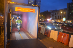 ©Barry Sandland/TIMB - Cyclist rides through a container tunnel in Brussels