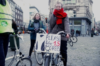 ©Barry Sandland/TIMB - Cyclists with a poster reading Please Below 1.5 degrees on the Climate Change protest ride